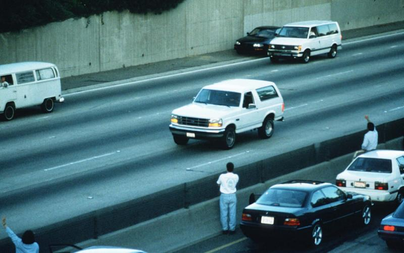 Al Cowlings drives football star O.J. Simpson south on LA Highway 405 in a white Ford Bronco followed by police cars June 17, 1994 in Los Angeles, CA -  Jean-Marc Giboux/Getty Images