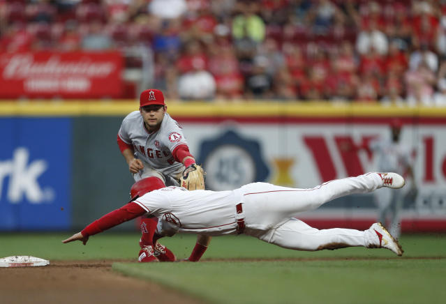 Cincinnati Reds' Jose Iglesias, bottom, is tagged out by Los Angeles Angels shortstop David Fletcher on a steal attempt during the fourth inning of a baseball game, Tuesday, Aug. 6, 2019, in Cincinnati. (AP Photo/Gary Landers)