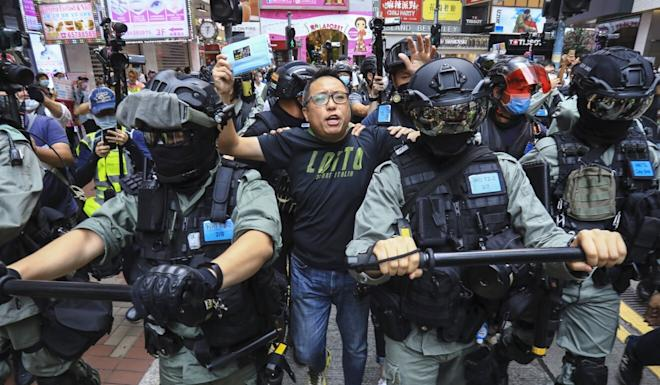 Tam Tak-chi is arrested near Causeway Bay's Sogo department store in May for his involvement in an unauthorised march against the national anthem law. Photo: May Tse