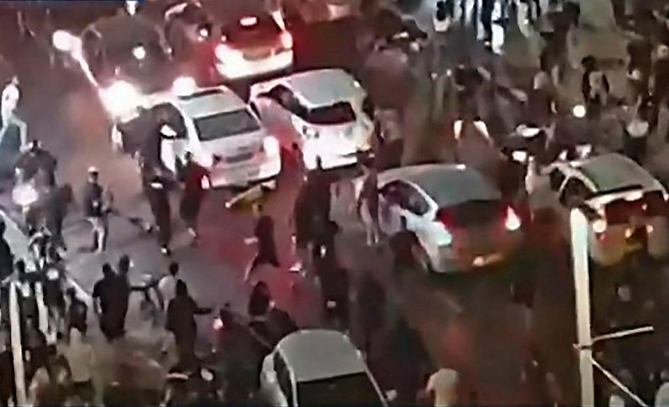 This video grab shows an Israeli mob attacking who they considered an Arab man on the seafront promenade of Bat YamKan 11 public proadcaster/AFP vi