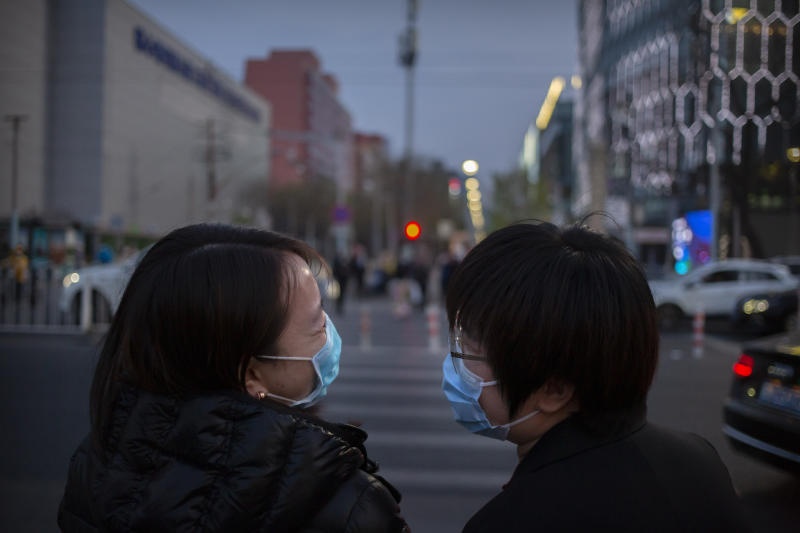 People wearing face masks to help curb the spread of the new coronavirus laugh as they cross an intersection in Beijing, Friday, April 10, 2020. China on Friday reported 42 new coronavirus cases, 38 of them imported, along with one additional death in the hardest-hit city of Wuhan. (AP Photo/Mark Schiefelbein)