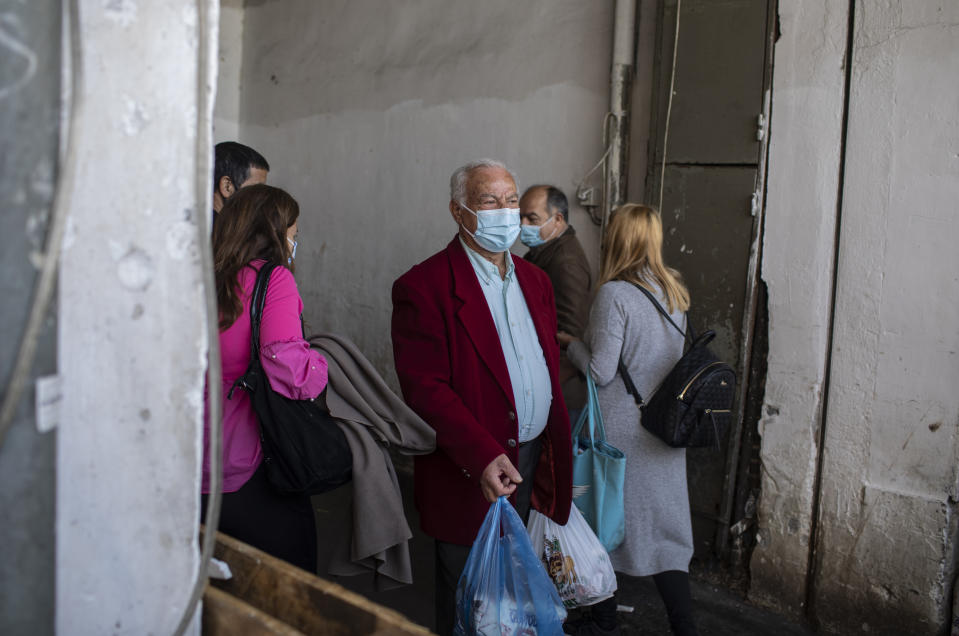 A consumer wearing a protective face mask carries bags as he exits the fish market of Athens during the Orthodox Holy Week, Thursday, April 29, 2021. (AP Photo/Petros Giannakouris)