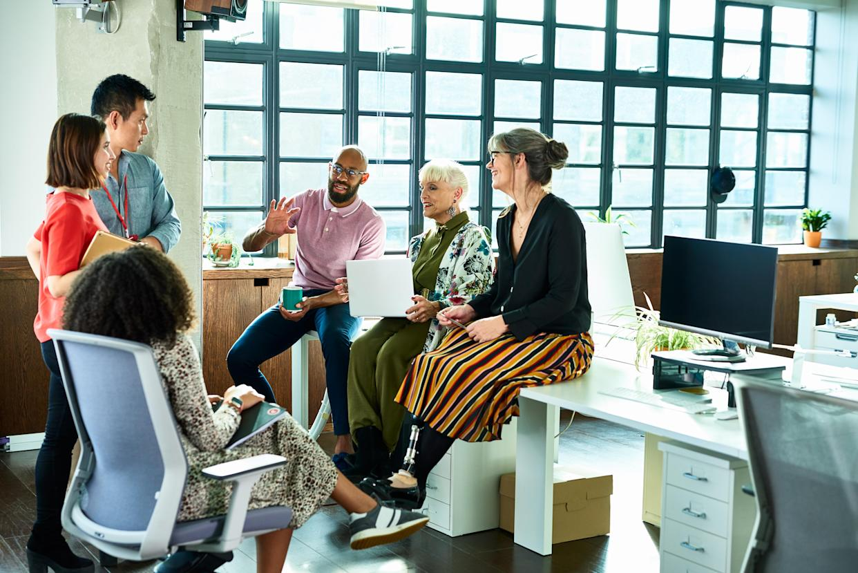A group of people having a discussion in an office