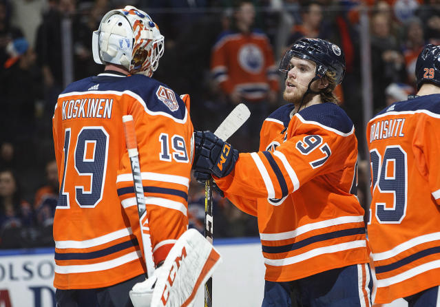 Edmonton Oilers goalie Mikko Koskinen (19) and Connor McDavid (97) celebrate the win over the Philadelphia Flyers during the third period of an NHL hockey game in Edmonton, Alberta, on Friday, Dec. 14, 2018. (Jason Franson/The Canadian Press via AP)