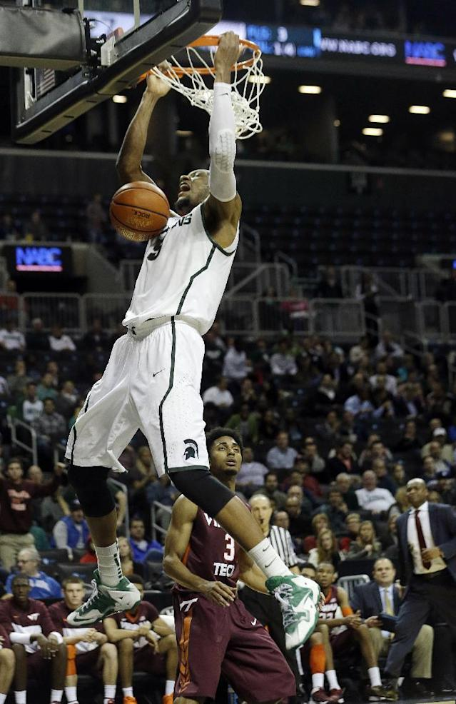 Michigan State's Adreian Payne (5) dunks the ball as Virginia Tech's Adam Smith (3) reacts during the first half of a Coaches vs. Cancer NCAA college basketball game on Friday, Nov. 22, 2013, in New York. (AP Photo/Frank Franklin II)