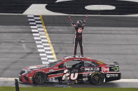 Christopher Bell stands on his car and celebrates in front of the grandstands after winning the NASCAR Cup Series road course auto race at Daytona International Speedway, Sunday, Feb. 21, 2021, in Daytona Beach, Fla. (AP Photo/John Raoux)