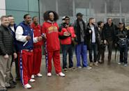 """Flamboyant former NBA star Dennis Rodman, fifth from right, poses with three members of the Harlem Globetrotters basketball team, in red jerseys, and a production crew for the media upon arrival at Pyongyang Airport, North Korea, Tuesday, Feb. 26, 2013. Rodman known as """"The Worm"""" arrived in Pyongyang, becoming an unlikely ambassador for sports diplomacy at a time of heightened tensions between the U.S. and North Korea. (AP Photo/Kim Kwang Hyon)"""