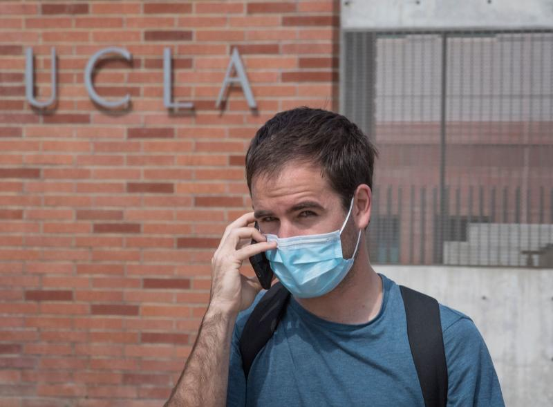 A man wears a face mask to protect against the COVID-19 (Coronavirus) as he leaves the campus of the UCLA college in Westwood, California on March 6, 2020. - Three UCLA students are currently being tested for the COVID-19 (coronavirus) by the LA Departement of Public Health, according to the UCLA Chancellor Gene Block. (Photo by Mark RALSTON / AFP) (Photo by MARK RALSTON/AFP via Getty Images)