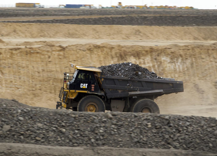 In this July 6, 2012 photo, a truck loaded with coal drives to a process station at Erdenes Tavan Tolgoi, a Mongolian state-owned coal mining company in Tavan Tolgoi, southern Mongolia. Chinese demand for copper and especially coal has propelled the Mongolian economy to one of the world's fastest growing, making some wealthy and driving down poverty in a still poor country, and China wants a larger share of the resources. (AP Photo/Andy Wong)