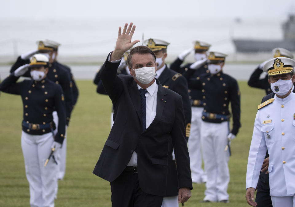 Brazilian President Jair Bolsonaro greets those gathered for a graduation ceremony at the Naval Academy, in Rio de Janeiro, Brazil, Saturday, June 19, 2021, amid the COVID-19 pandemic. People gathered across the country Saturday, to protest Bolsonaro's handling of the pandemic and economic policies protesters say harm the interests of the poor and working class. (AP Photo/Silvia Izquierdo)