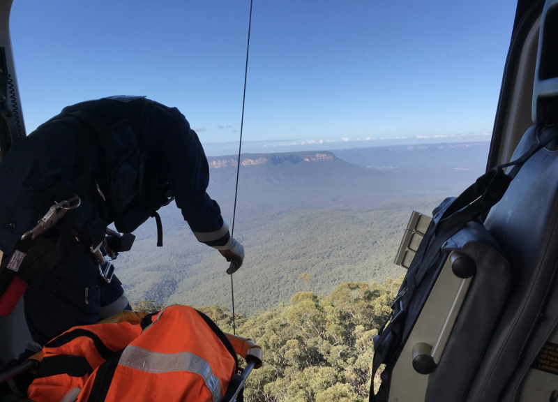 Pictured is a member of a crew looking out of a helicopter's open door. Source: Toll