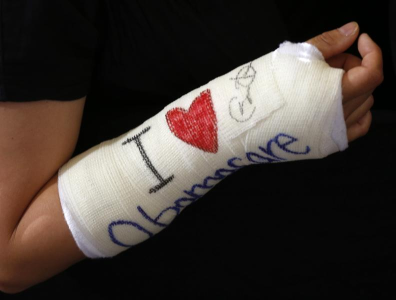 """Cathey Park of Cambridge, Massachusetts shows her cast signed by U.S. President Barack Obama after he spoke about health insurance at Faneuil Hall in Boston October 30, 2013. The writing on the cast reads, """"I Love Obamacare."""" REUTERS/Kevin Lamarque (UNITED STATES - Tags: POLITICS HEALTH)"""