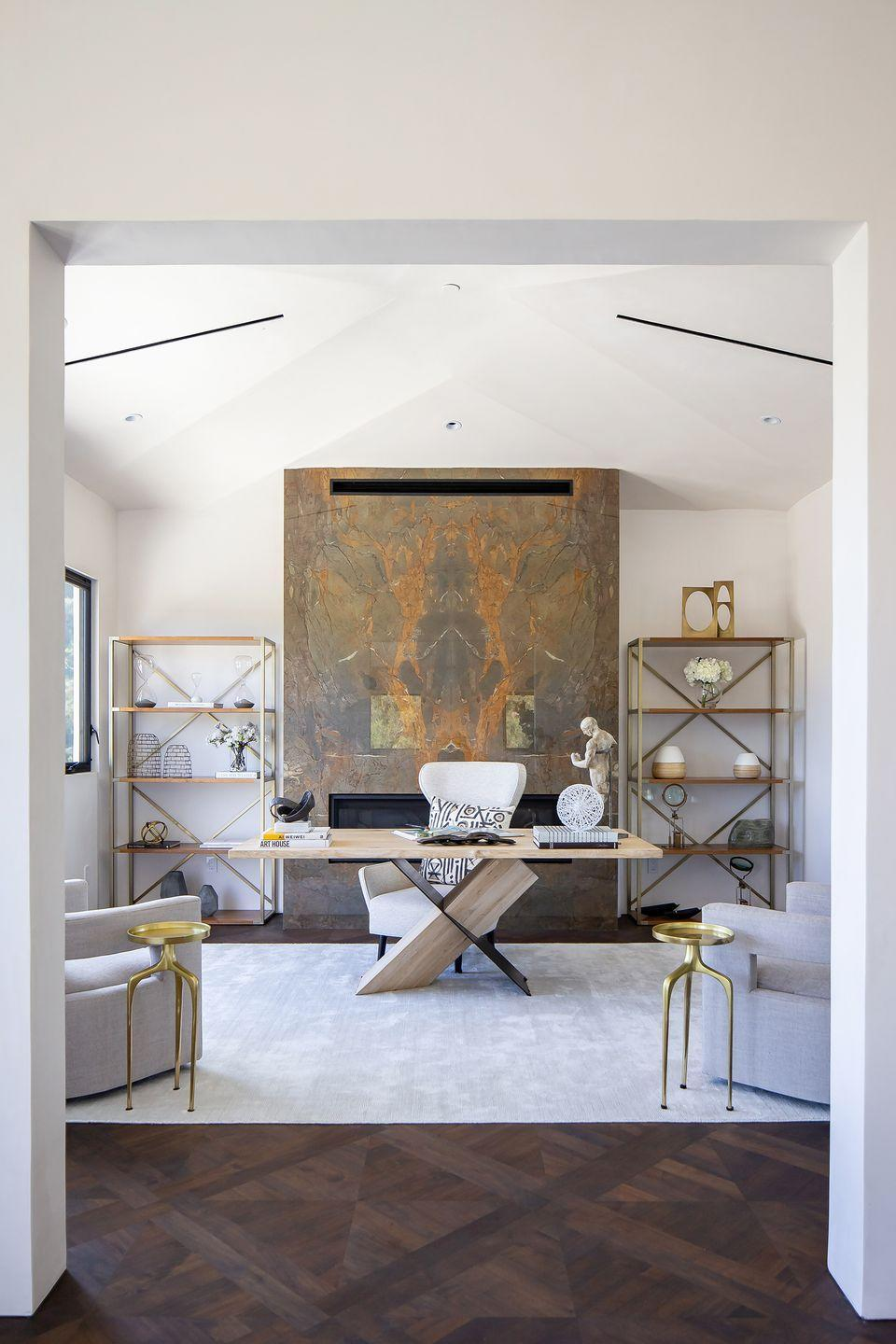 """<p>Warm up an open and airy home office with a fireplace that features an earth-toned facade, like this one in a large space <a href=""""https://www.housebeautiful.com/design-inspiration/house-tours/a33930929/breegan-jane-unica-tour/"""" rel=""""nofollow noopener"""" target=""""_blank"""" data-ylk=""""slk:designed"""" class=""""link rapid-noclick-resp"""">designed</a> by <a href=""""https://breeganjane.com/"""" rel=""""nofollow noopener"""" target=""""_blank"""" data-ylk=""""slk:Breegan Jane."""" class=""""link rapid-noclick-resp"""">Breegan Jane.</a> The marble introduces sophisticated, formal style to the more casual elements but it also helps to bring the scale of the ceilings down to a more intimate, human scale. </p>"""