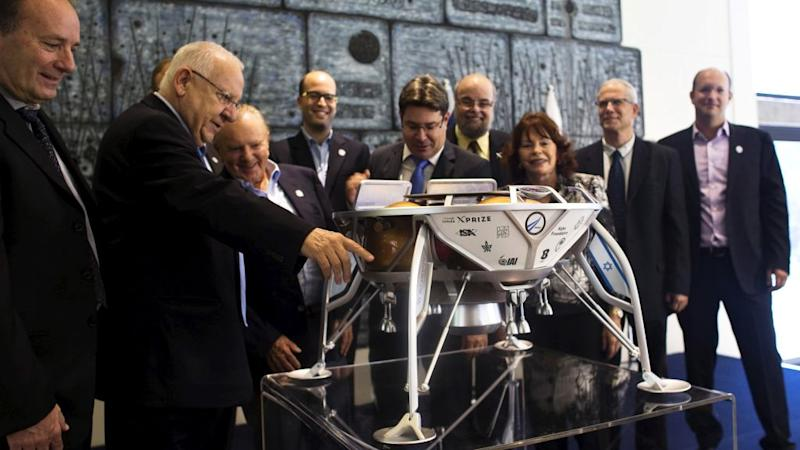 Israeli President Reuven Rivlin (2nd L), Minister of Science, Technology and Space, Ofir Akunis (5th L) and members of the Israeli team, SpaceIL, look at a model of an Israeli spacecraft, during a meeting in Jerusalem October 7, 2015. The Israeli team competing in a race to the moon sponsored by Google has signed a with California-based SpaceX for a rocket launch, putting it at the front of the pack and on target for blast-off in late 2017, officials said on Wednesday.