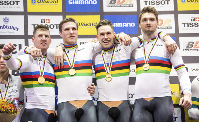The team from the Netherlands, Roy van den Berg, Jeffrey Hoogland, Harrie Lavreysen and Matthijs Buchli celebrate during the winners ceremony, after winning the gold medal in the team sprint competition during the Track Cycling World Championships in Berlin, Germany, Wednesday, Feb. 26, 2020. ( Sebastian Gollnow/dpa via AP)