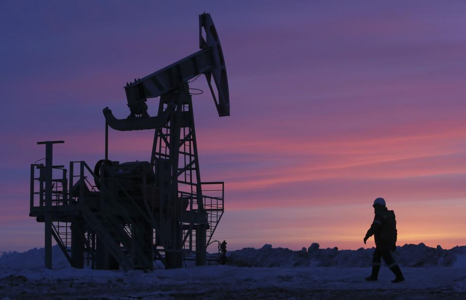 A worker walks past a pump jack on an oil field owned by Bashneft company near the village of Nikolo-Berezovka, northwest from Ufa, Bashkortostan, January 28, 2015. New European Union sanctions against Russia could include further capital markets restrictions, making it harder for Russian companies to refinance themselves and possibly affecting Russian sovereign bonds and access to advanced technology for the oil and gas sectors, EU officials said on Wednesday. REUTERS/Sergei Karpukhin (RUSSIA - Tags: ENERGY BUSINESS INDUSTRIAL POLITICS)