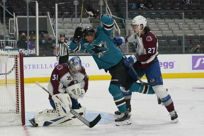 Colorado Avalanche goaltender Philipp Grubauer, left, grabs the puck in front of defenseman Ryan Graves (27) and San Jose Sharks left wing Evander Kane, middle, during the first period of an NHL hockey game in San Jose, Calif., Monday, May 3, 2021. (AP Photo/Jeff Chiu)
