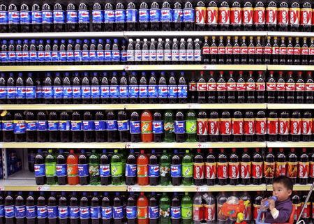 File photo of a boy sitting in a toy tricycle being pushed past shelves of bottled beverages at a supermarket in Nanjing