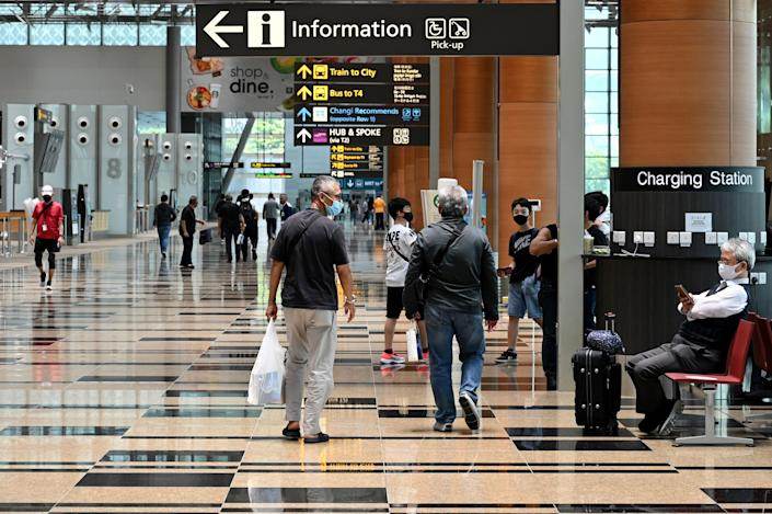 A traveller (R) waits in the departure hall of Changi International Airport in Singapore on March 15, 2021. (Photo by Roslan RAHMAN / AFP) (Photo by ROSLAN RAHMAN/AFP via Getty Images)