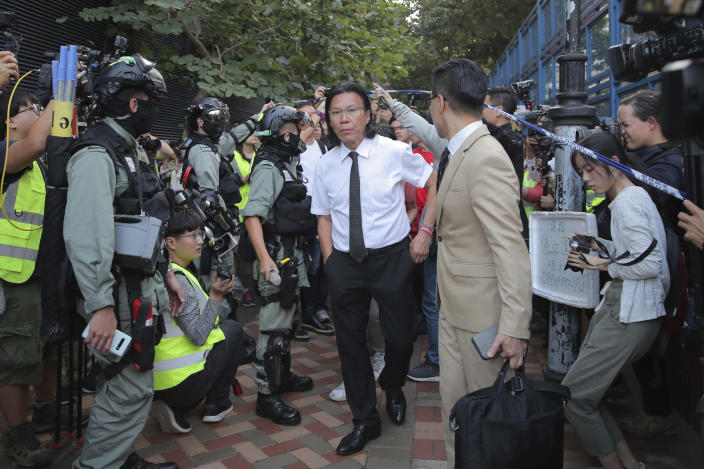 In this Monday, Nov. 25, 2019, photo, lawyer Daniel Wong Kwok-tung, center, arrives at the Polytechnic University to meet the protesters in Hong Kong. Hong Kong national security police on Thursday, Jan. 14, 2021, arrested a lawyer and 10 others on suspicion of helping 12 Hong Kongers try to flee the city, local media reported in the latest arrests in an ongoing crackdown on dissent. Wong, a member of the city's Democratic Party, is known for providing legal assistance to hundreds of protesters arrested during the anti-government protests in Hong Kong in 2019. (AP Photo/Kin Cheung)