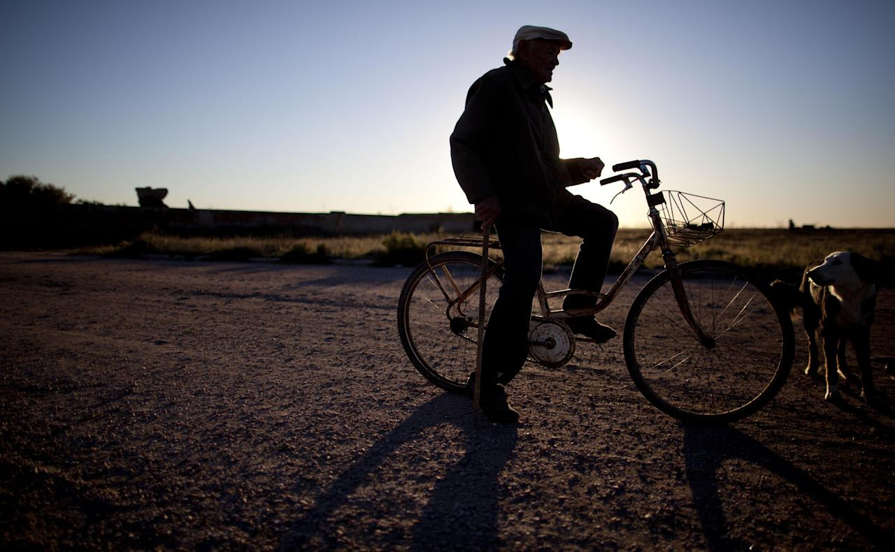 In this May 6, 2013 photo, Pablo Novak sits on his bike in Epecuen, a village that was once submerged by water in Argentina. Many residents of Epecuen fled to nearby Carhue, another lakeside town, and set up new hotels and spas, promising relaxing getaways featuring saltwater and mud facials.(AP Photo/Natacha Pisarenko)