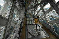 A visitor walks over the glass walkway at the Tower Bridge Visitor Attraction, in London, on the first day it was allowed to reopen as the British government relaxes its third coronavirus lockdown restrictions, Monday, May 17, 2021. (AP Photo/Matt Dunham)