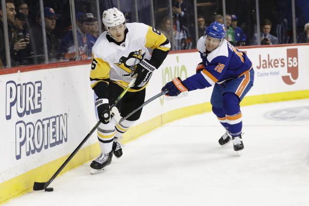 New York Islanders' Josh Bailey (12) fights for control of the puck with Pittsburgh Penguins' John Marino (6) during the second period of an NHL hockey game Thursday, Nov. 21, 2019, in New York. (AP Photo/Frank Franklin II)