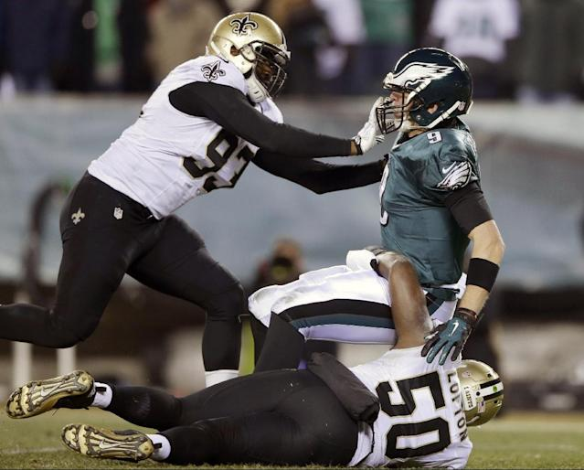Philadelphia Eagles' Nick Foles, top right, is tackled by New Orleans Saints' Junior Galette, left, and Curtis Lofton during the second half of an NFL wild-card playoff football game, Saturday, Jan. 4, 2014, in Philadelphia. (AP Photo/Michael Perez)