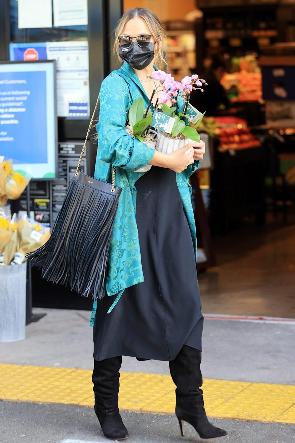<p>Chrissy Teigen picks up some flowers while shopping in L.A. with her mom on Monday. </p>