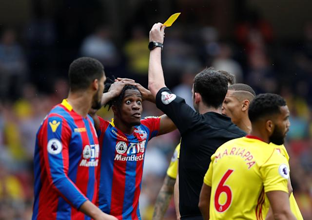 """Soccer Football - Premier League - Watford v Crystal Palace - Vicarage Road, Watford, Britain - April 21, 2018 Crystal Palace's Wilfried Zaha is shown a yellow card by referee Chris Kavanagh for simulation Action Images via Reuters/Paul Childs EDITORIAL USE ONLY. No use with unauthorized audio, video, data, fixture lists, club/league logos or """"live"""" services. Online in-match use limited to 75 images, no video emulation. No use in betting, games or single club/league/player publications. Please contact your account representative for further details."""