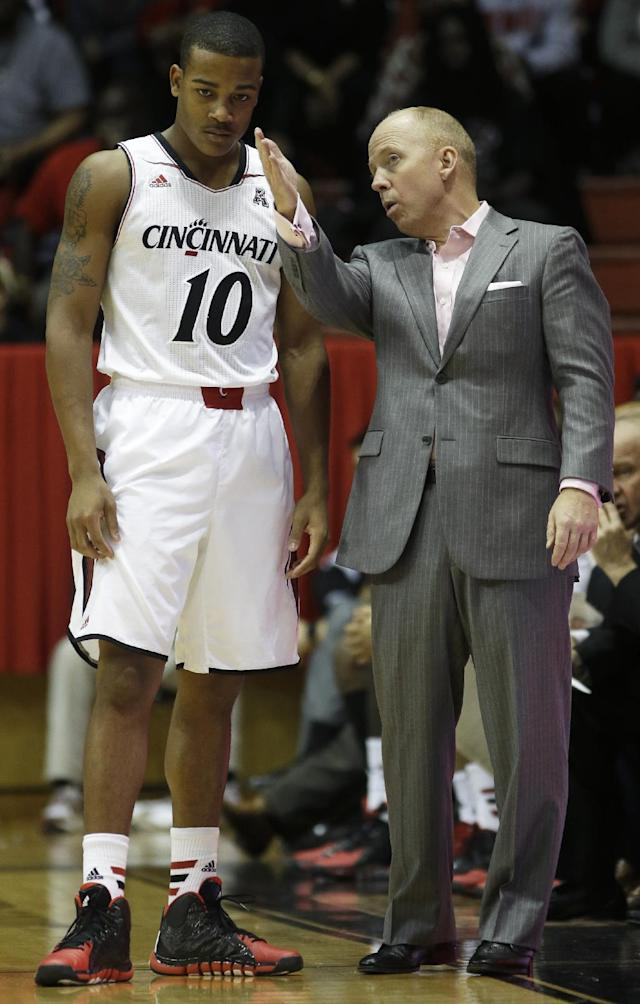 Cincinnati head coach Mick Cronin talks with guard Troy Caupain (10) in the second half of an exhibition NCAA college basketball game against Carleton, Saturday, Oct. 26, 2013, in Cincinnati. (AP Photo/Al Behrman)