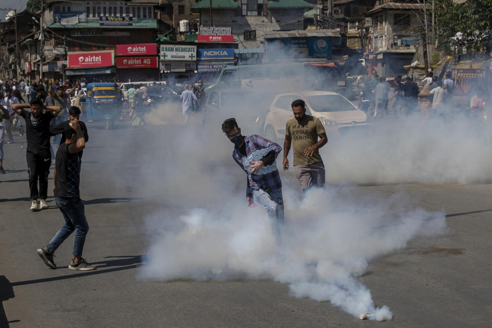 A Kashmiri Shiite mourner kicks an exploded tear gas canister during a religious procession in central Srinagar, Indian controlled Kashmir, Tuesday, Aug. 17, 2021. Police in Indian-controlled Kashmir on Tuesday fired tear gas and warning shots to disperse hundreds of Shiite Muslims, while detaining dozens who attempted to participate in processions marking the Muslim month of Muharram. (AP Photo/Dar Yasin)