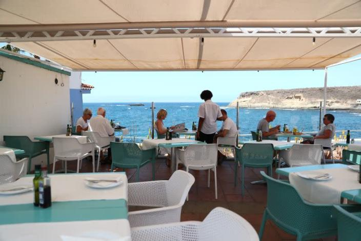 "Waiter Yamilca attends tourists in a terrace of an almost empty restaurant ""Celso"" at La Caleta beach in Adeje"