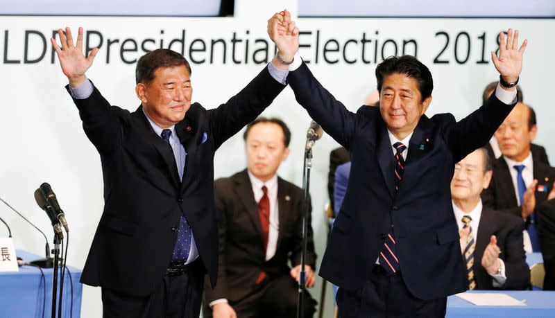 Japan's PM Abe, who is also the ruling LDP leader, raises his hands with former defence minister Ishiba after Abe won the ruling party leadership vote at the party's headquarters in Tokyo