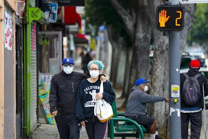 LOS ANGELES, CA - APRIL 11: A couple in face masks walk down Cesar E. Chavez Blvd on Saturday morning in Los Angeles. Life around Cesar E. Chavez Blvd. and Soto St. has slow down as California officials extended stay-at-home orders into May and residents entered Easter weekend with unprecedented limits on their movements. Most of the people are adhering to the orders by mayor to wear masks while out running errands. Los Angeles, CA. (Irfan Khan / Los Angeles Times)