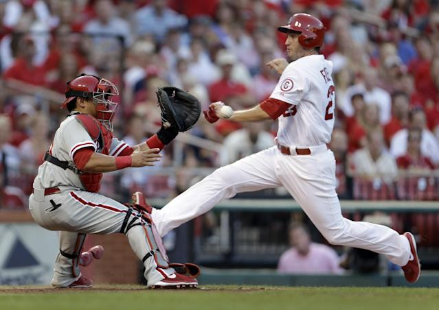 Philadelphia Phillies catcher Carlos Ruiz, left, prepares to tag St. Louis Cardinals' David Freese out at home during the second inning of a baseball game on Wednesday, July 24, 2013, in St. Louis. Freese tried to score on a fly out by Pete Kozma. (AP Photo/Jeff Roberson)