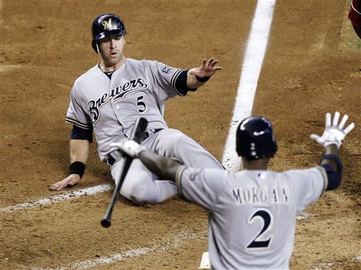Milwaukee Brewers' Taylor Green, top, slides across home plate to score a run against the Arizona Diamondbacks as Nyjer Morgan, bottom, watches in the fifth inning of a baseball game, Sunday, May 27, 2012, in Phoenix. (AP Photo/Paul Connors)