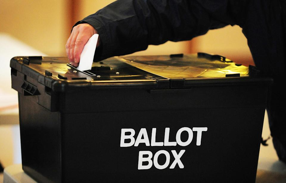 A voter places a ballot paper in the ballot box at the polling station at Market Hall in Swadlincote, Derbyshire, as the General Election got underway across the UK.