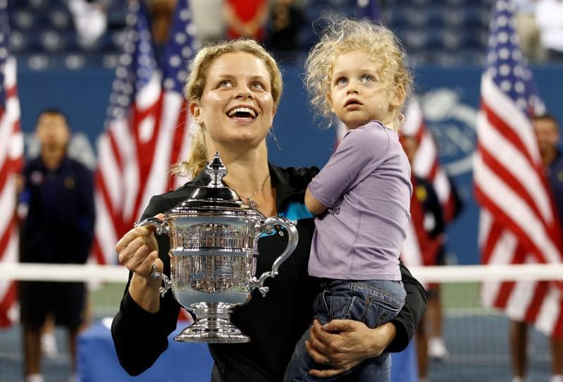 FILE PHOTO: Kim Clijsters holds her daughter as she poses with her trophy after defeating Vera Zvonareva during the U.S. Open tennis tournament in New York