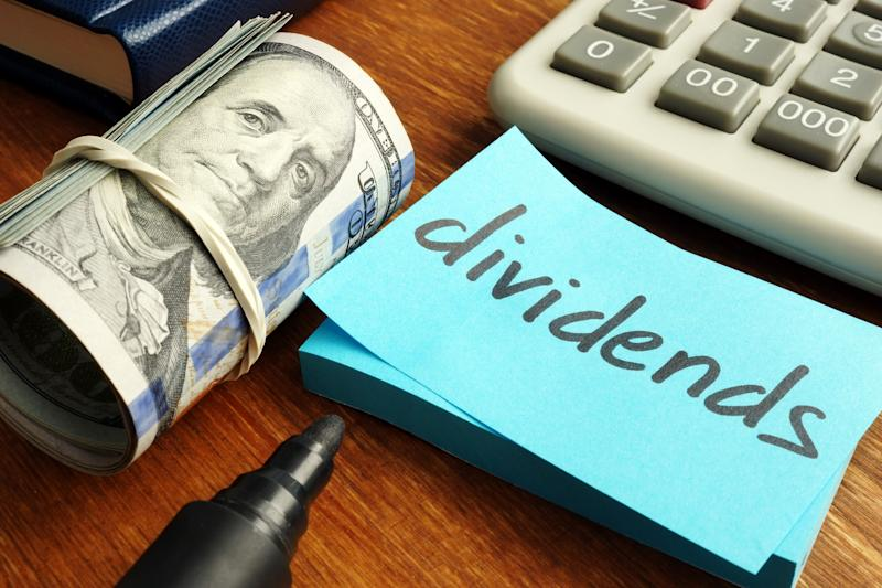 The word dividends written on a sticky note pad that's next to a roll of cash and a calculator.