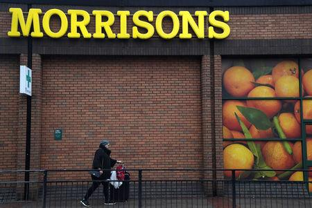 FILE PHOTO: A shopper walks past a branch of the food retailer Morrisons in west London, Britain
