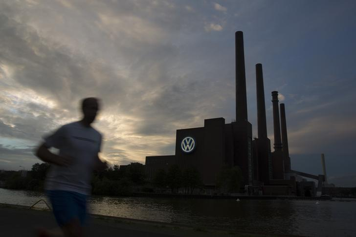 Jogger runs along bank of Midland Canal in front of Volkswagen power plant in Wolfsburg