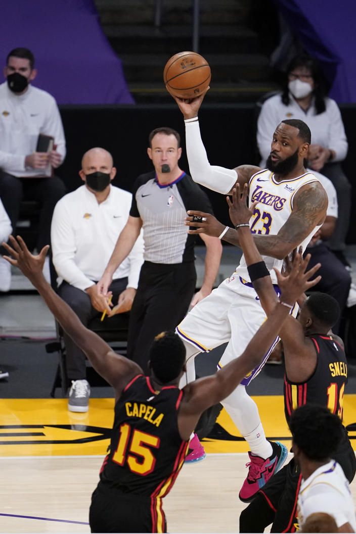 Los Angeles Lakers forward LeBron James, top, passes over Atlanta Hawks center Clint Capela (15) and forward Tony Snell during the first half of an NBA basketball game Saturday, March 20, 2021, in Los Angeles. (AP Photo/Marcio Jose Sanchez)