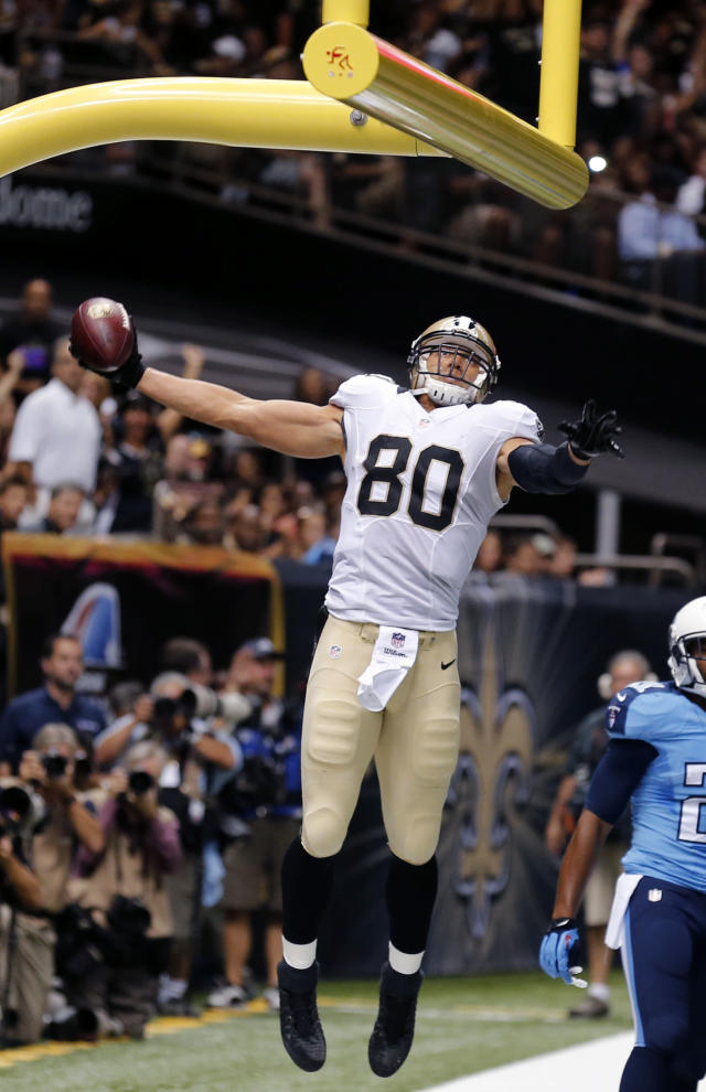 New Orleans Saints tight end Jimmy Graham (80) slam dunks over the goal post after scoring on a touchdown reception in the first half of a NFL preseason football game against the Tennessee Titans in New Orleans, Friday, Aug. 15, 2014. (AP Photo/Bill Haber)