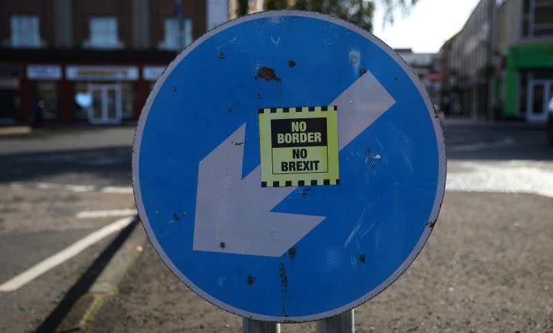 A 'No hard Border' poster is seen below a road sign on the Irish side of the border between Ireland and Northern Ireland near Bridgend Ireland