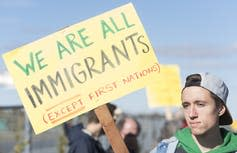 A man holds a sign that reads We Are All Immigrants (Except First Nations)