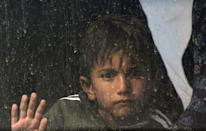 An Iraqi boy sits in a bus transporting displaced families from the camp in Habbaniyah