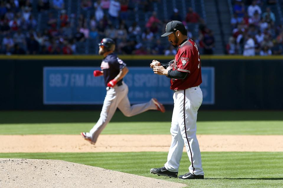 Arizona Diamondbacks pitcher Fernando Salas, right, rubs up a new baseball after giving up a home run to Cleveland Indians' Mike Napoli, left, during the sixth inning of a spring training baseball game Tuesday, March 27, 2018, in Phoenix. (AP Photo/Ross D. Franklin)