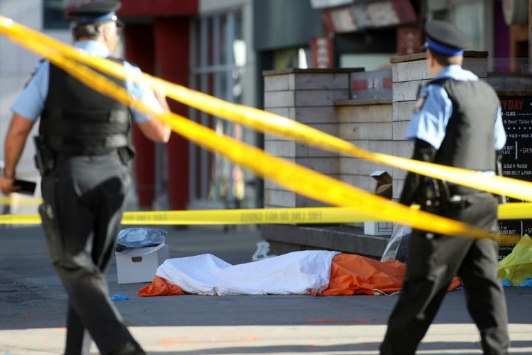 Police officers stand near one of the bodies of the victims in downtown Toronto