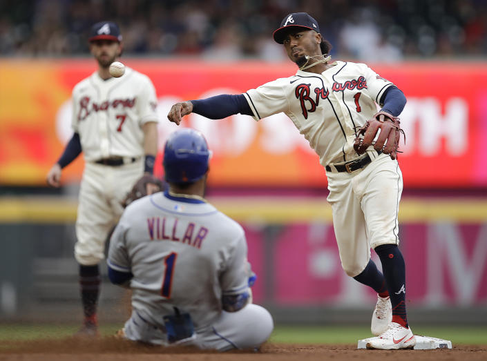 Atlanta Braves' Ozzie Albies, right, throws over New York Mets' Jonathan Villar (1) to complete a double play in the fifth inning of a baseball game Sunday, Oct. 3, 2021, in Atlanta. Mets' Jose Peraza was out at first base. (AP Photo/Ben Margot)